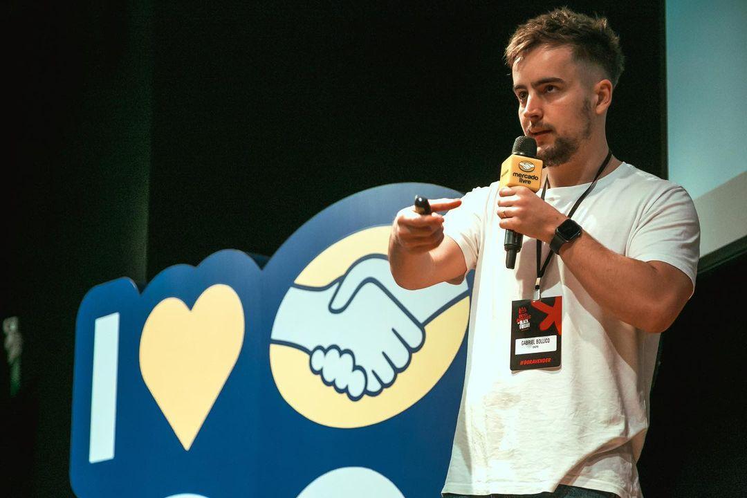 Gabriel Bollico com um microfone na mão, palestrando.