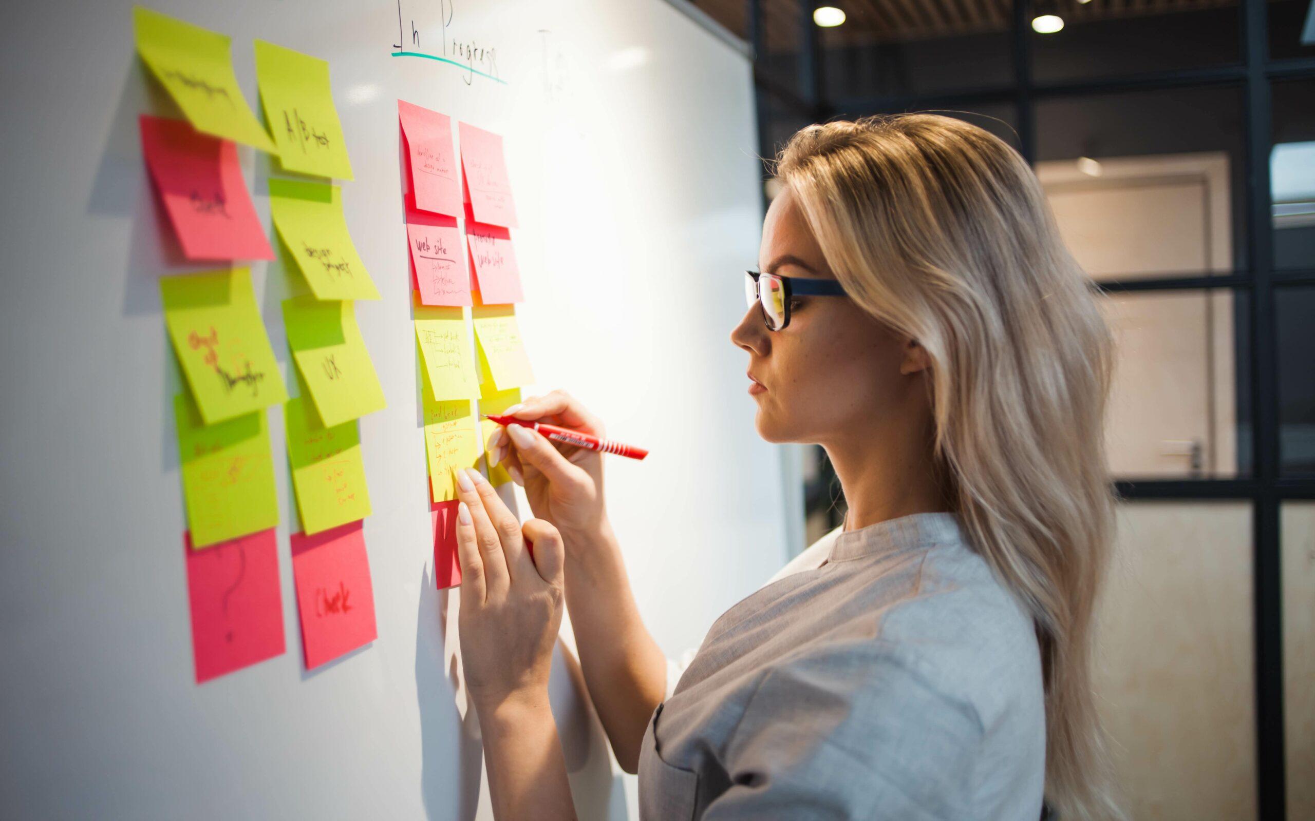 Mulher organizando processos e tarefas em post-its colados na parede.