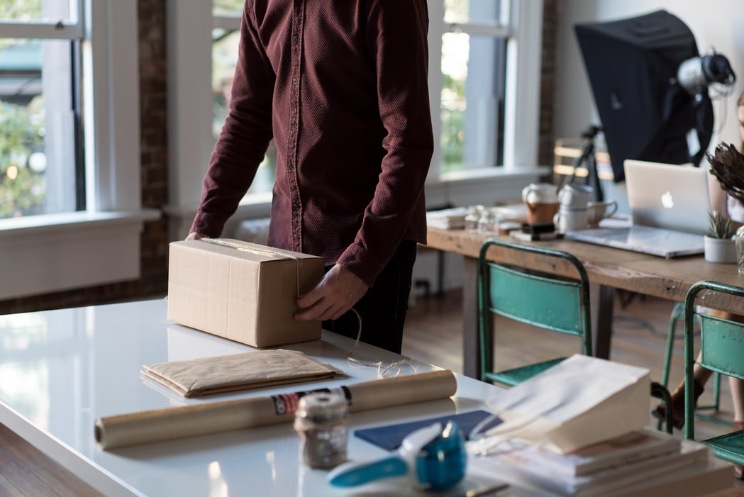 Homem realizando o empacotamento de determinado produto.