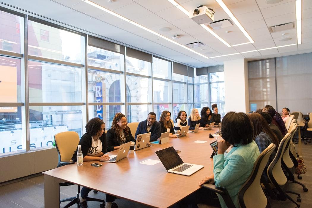 Equipe de trabalho reunida em mesa de reunião.