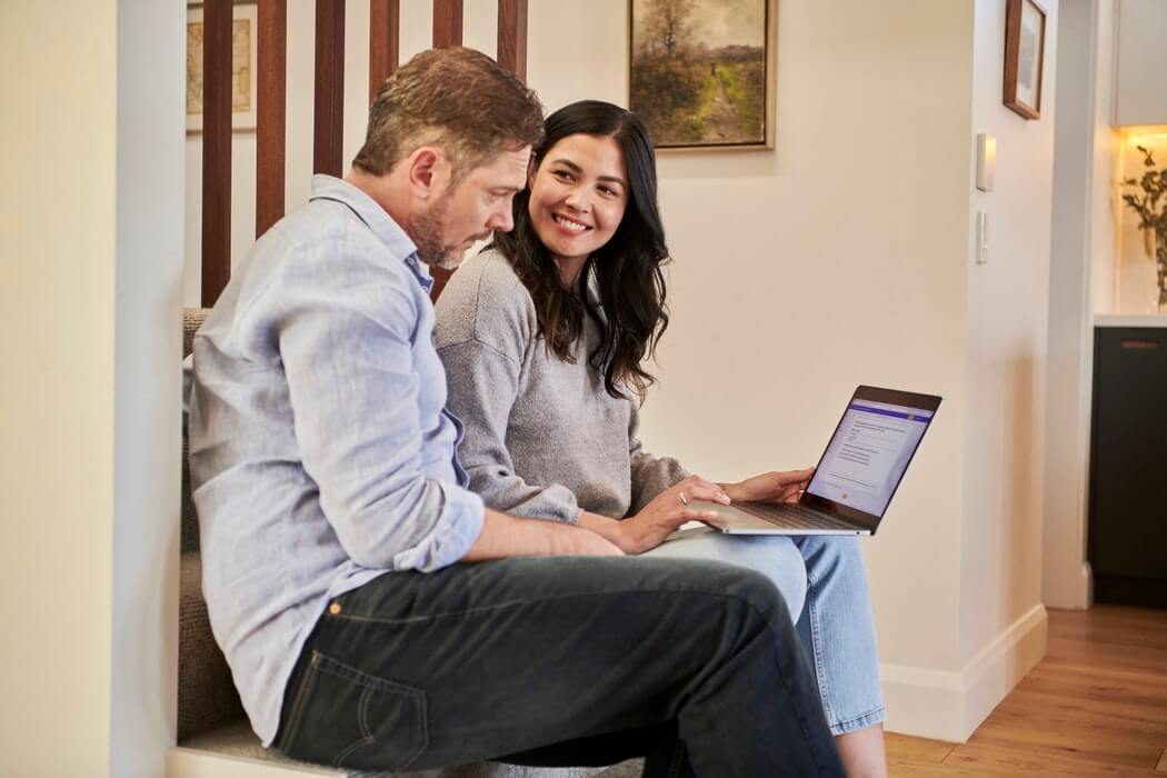 Homem e mulher de negócios analisando dados em notebook.