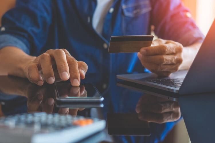 Pessoa realizando compra pelo celular com cartão de crédito.