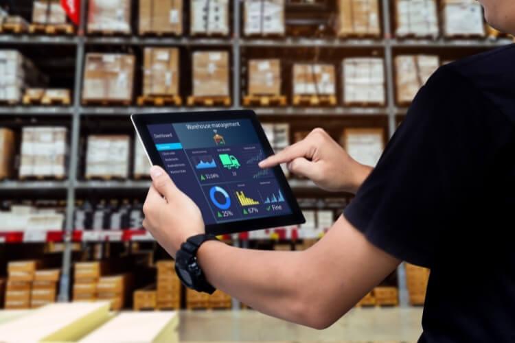 Pessoa realizando análise dos dados do estoque em tablet.