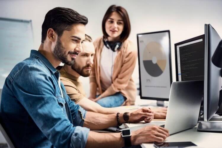 Três funcionários analisando dados em telas de computadores.