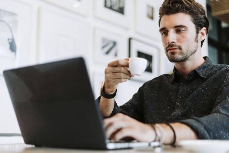 Homem bebendo café e mexendo no notebook.