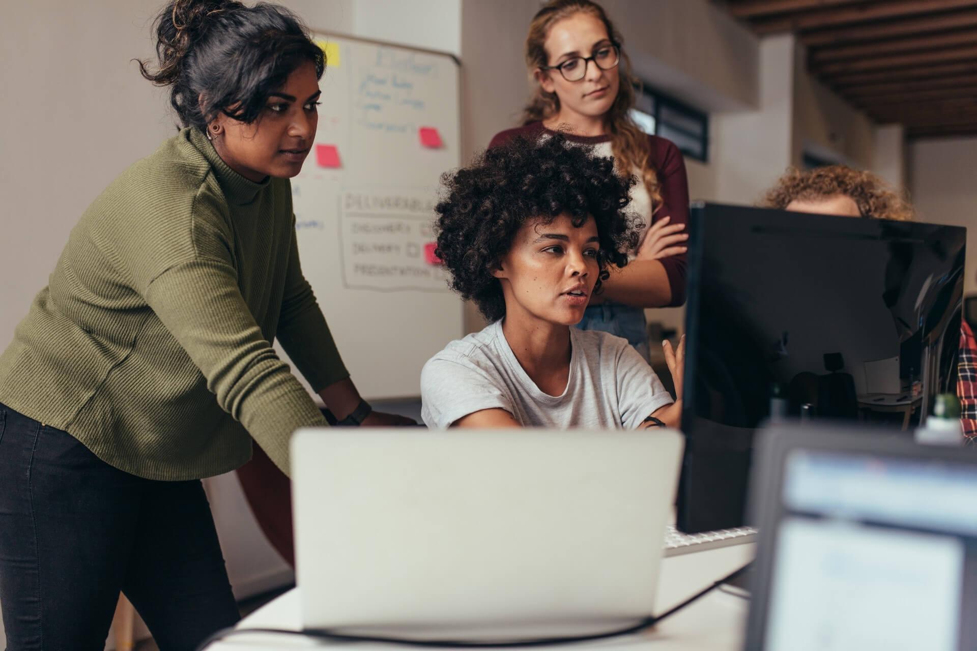 Equipe de trabalho ao redor de um computador.