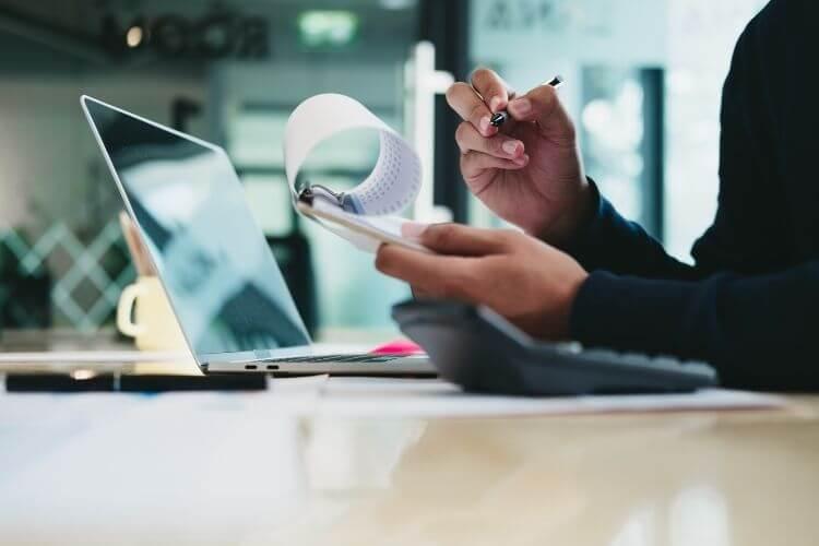Pessoa anotando em prancheta com papéis, com notebook ao fundo.