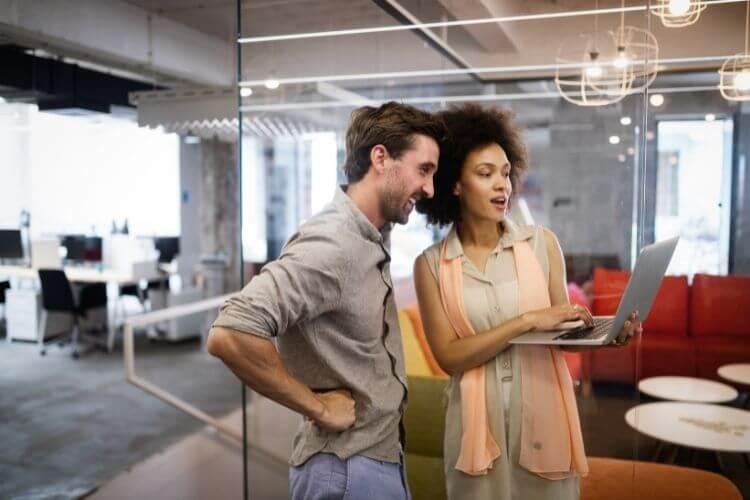 Homem e mulher de trabalho em escritório, olhando para notebook.