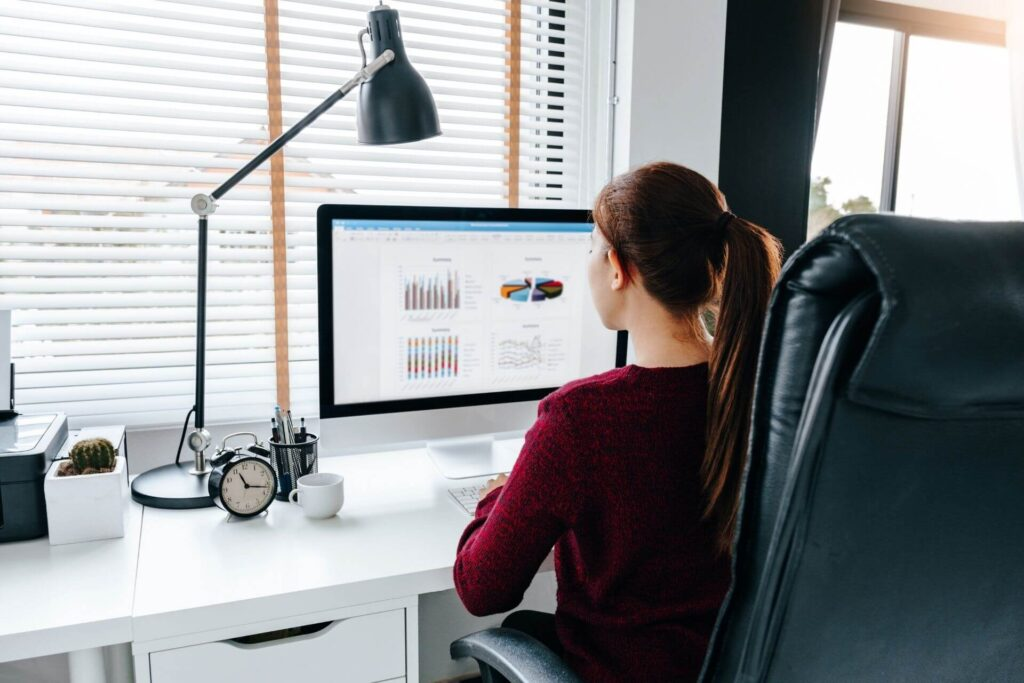 Mulher no computador analisando dados da pesquisa de marketplace.