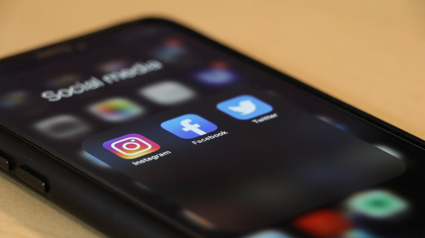 Celular com pasta de redes sociais, mostrando Facebook, Instagram e outras.